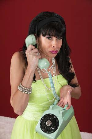 rotary dial telephone: Hacer pucheros de estilo retro mujer sostiene tel�fono de disco