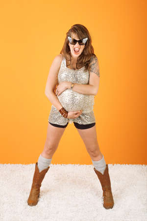 Excited pregnant woman with huge sunglasses over orange background photo