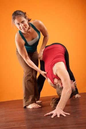Yoga instructor helping student stretch over orange background photo