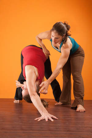 Yoga trainer helping young woman perform exercises photo