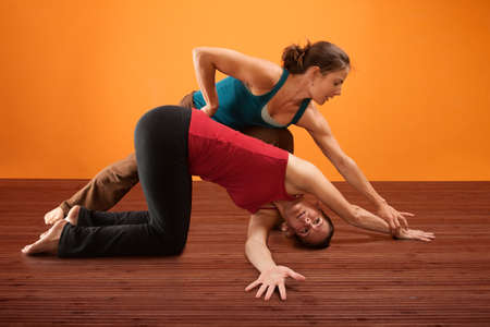 helps: Yoga instructor helps student with stretching her shoulders Stock Photo