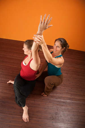 Yoga coach helping student stretch shoulders photo