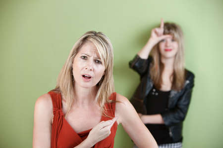 Frustrated woman points at girl showing loser sign photo