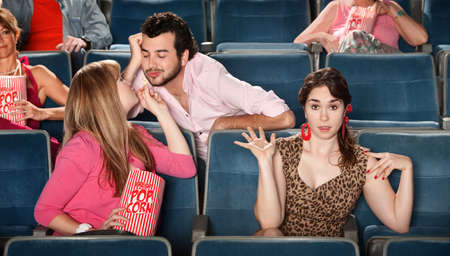 embarrassing: Man flirting with girl next to embarrassed friend in theater