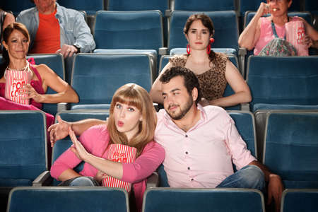 misbehaving: Young woman annoyed with boyfriend in theater