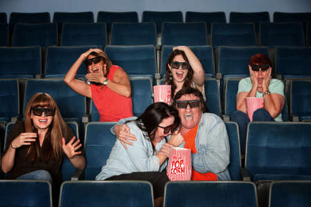 3d scary: Group of scared people with 3d glasses screaming in a theater Stock Photo