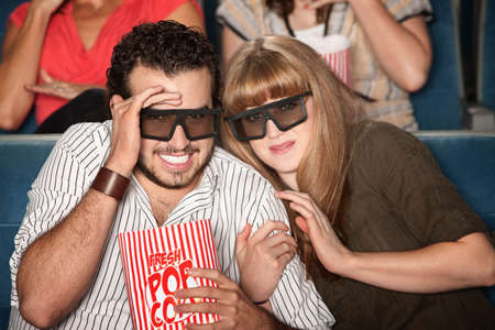 Couple with 3D glasses and popcorn flinching photo