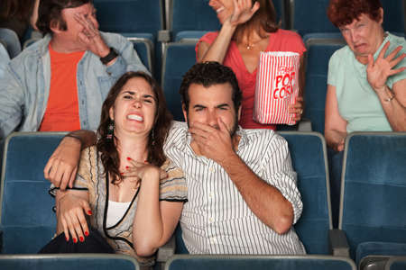 Disgusted people watch movie in a theater photo