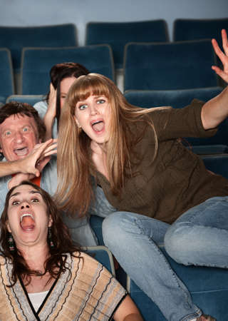 Scared Caucasian teen jumps out of her seat in theater photo