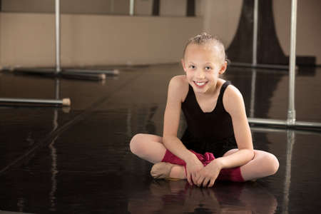 Cute young ballerina sitting on a dance floor photo