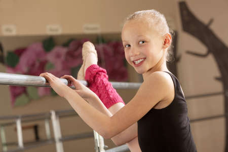 Little ballerina girl with leg on bar in dance studio photo