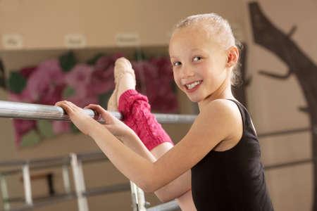 Little ballerina girl with leg on bar in dance studio