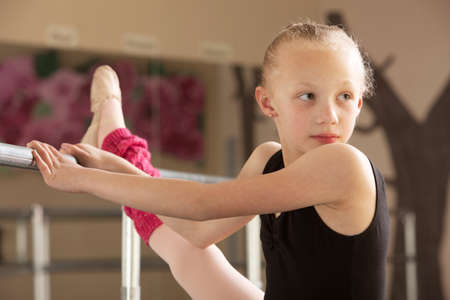 ballet bar: Serious child ballet student looks over her shoulder Stock Photo