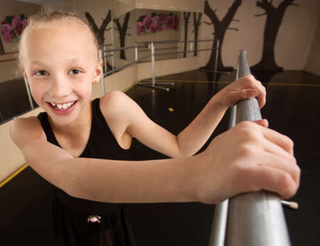 ballet bar: Cute mixed race ballerina in dance studio