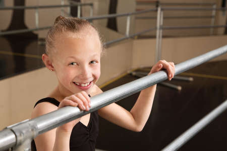 Smiling cute ballet student holds railing in dance studio photo
