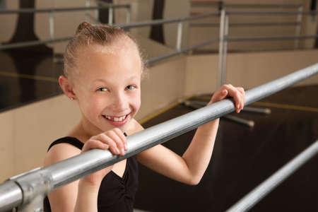 Smiling cute ballet student holds railing in dance studio Zdjęcie Seryjne