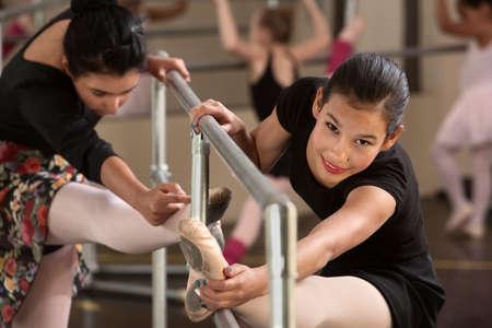 niños latinos: Bastante niñas hispanas de calentamiento en una clase de ballet