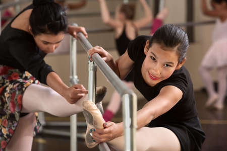 ballet slippers: Pretty Hispanic girls warming up in a ballet class