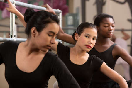 teenaged girls: Serious mixed group of girls working out for ballet class