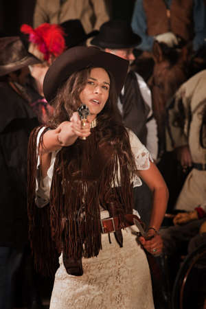 gunfighter: Sassy Latina woman in western outfit with pistol and dagger Stock Photo