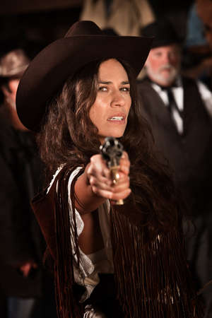 Mexican woman in old west style clothes points a revolver photo