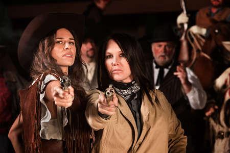 gunfighter: Serious ladies in western wear draw their revolvers