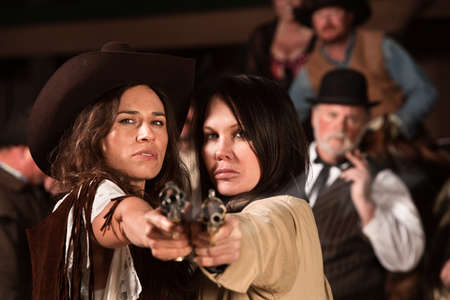 gunfighter: Two pretty cowgirls point revolvers at the camera