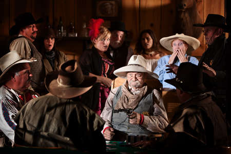 saloon: Elderly man holds up players in a poker game Stock Photo