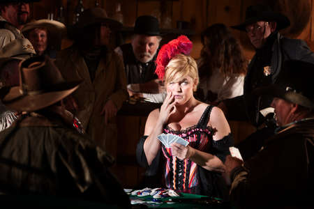 Bluffing bar maid with playing cards in old west saloon