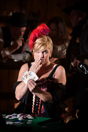 Pretty showgirl with hand over mouth and playing cards