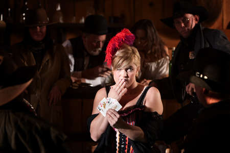 Embarrassed prostitute with hand of cards at poker table Stock Photo - 13670047