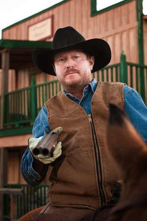 Tough old west cowboy on horseback with shotgun photo