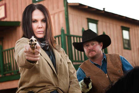 Pretty woman and partner aim guns in old west town photo