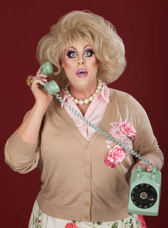 drag queen: Surprised drag queen holding telephone over maroon background