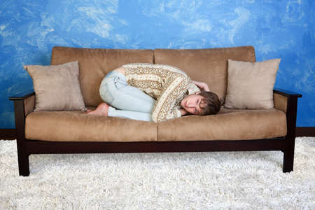 curledup: Caucasian teen in curled up position on sofa