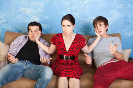 Angry young woman slaps two men on sofa