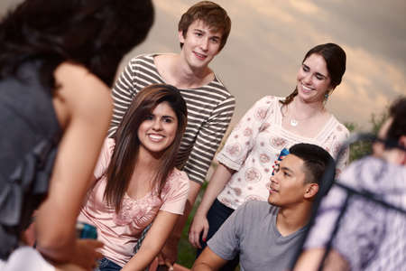 Group of six happy young people outside photo