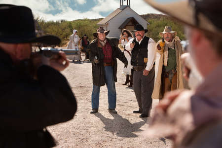 Cowboys pull out their weapons in an old west shoot out photo