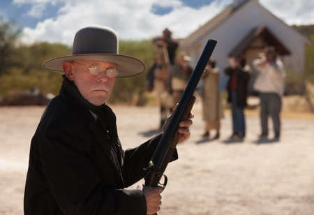 outlaws: Brave old west cowboy under attack from outlaws Stock Photo