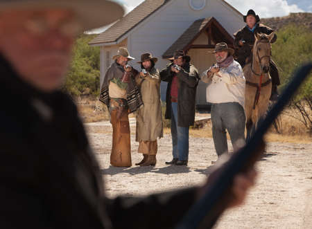 Rowdy: Six old west gunfighters target a man in black Stock Photo