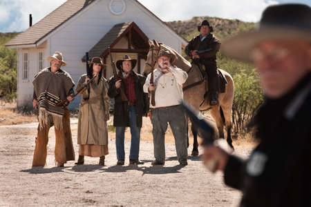 gunfighter: Gang of outlaws with rifles in old American west town