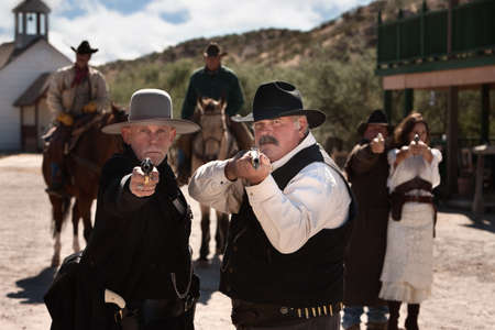 Brave men aim their guns in old west town photo
