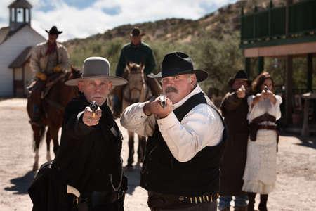 hombre disparando: Los hombres valientes apuntan sus armas de fuego en el viejo oeste de la ciudad