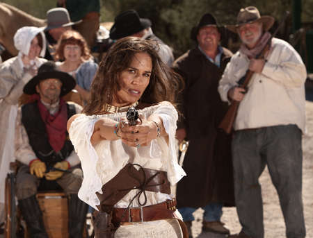 Mexican woman in old west style clothes points her gun photo