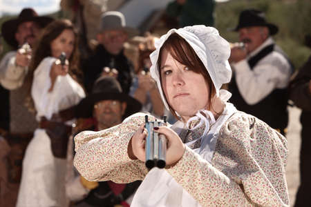 Serious young lady in bonnet pointing a double barrel shotgun