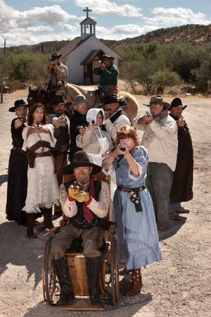 People in American old west scene with weapons in front of church photo