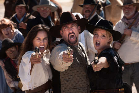 Three gunfighters yell while shooting in outdoor old west scene photo