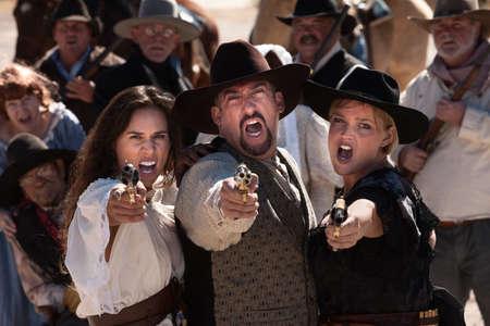 hombre disparando: Tres pistoleros grita mientras se dispara en la escena al aire libre viejo oeste