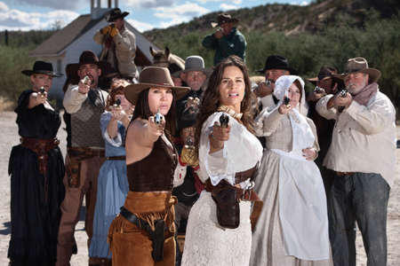 Pretty gunfighters lead armed crowd outside in American west town photo
