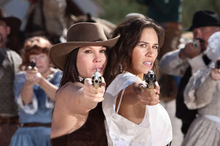Pretty female gunfighters with pistols at point blank range Stock Photo